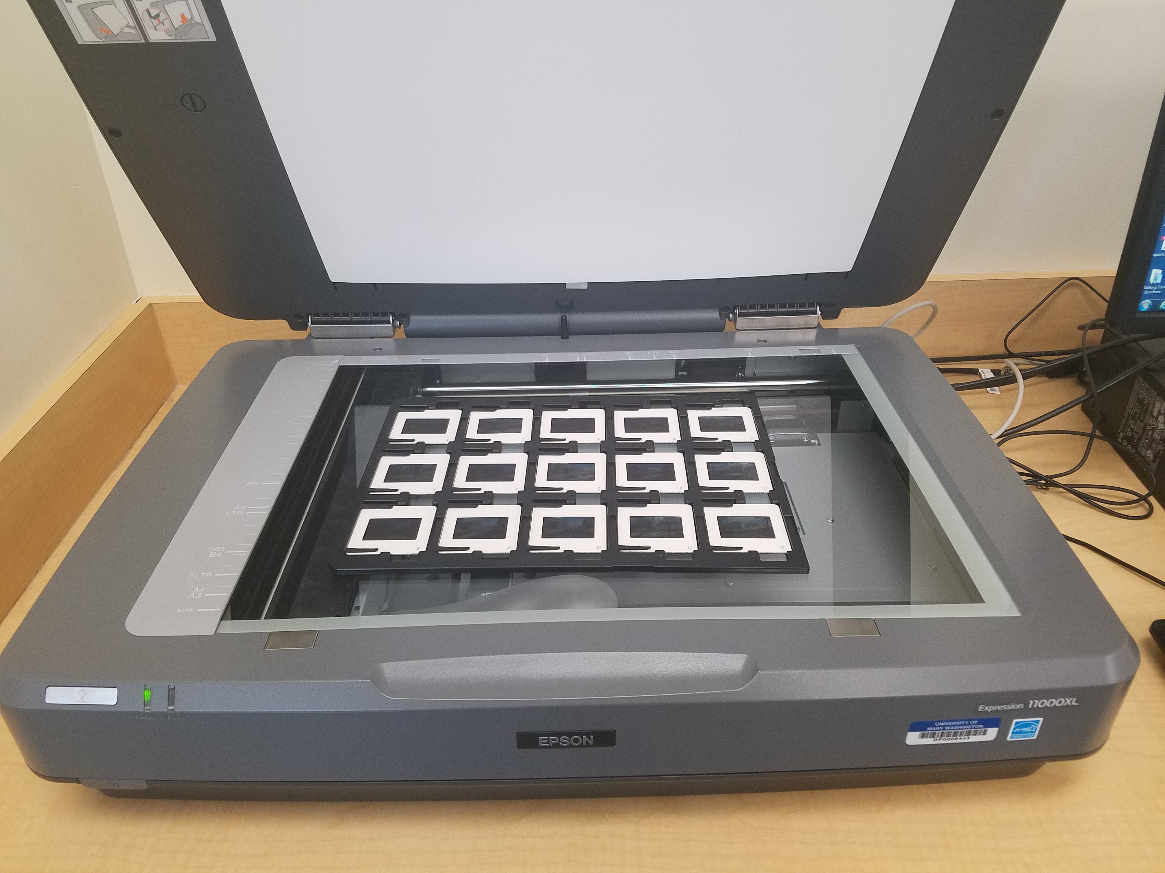 Photograph of a flatbed scanner with its lid open, and a tray of slide film sitting on top.