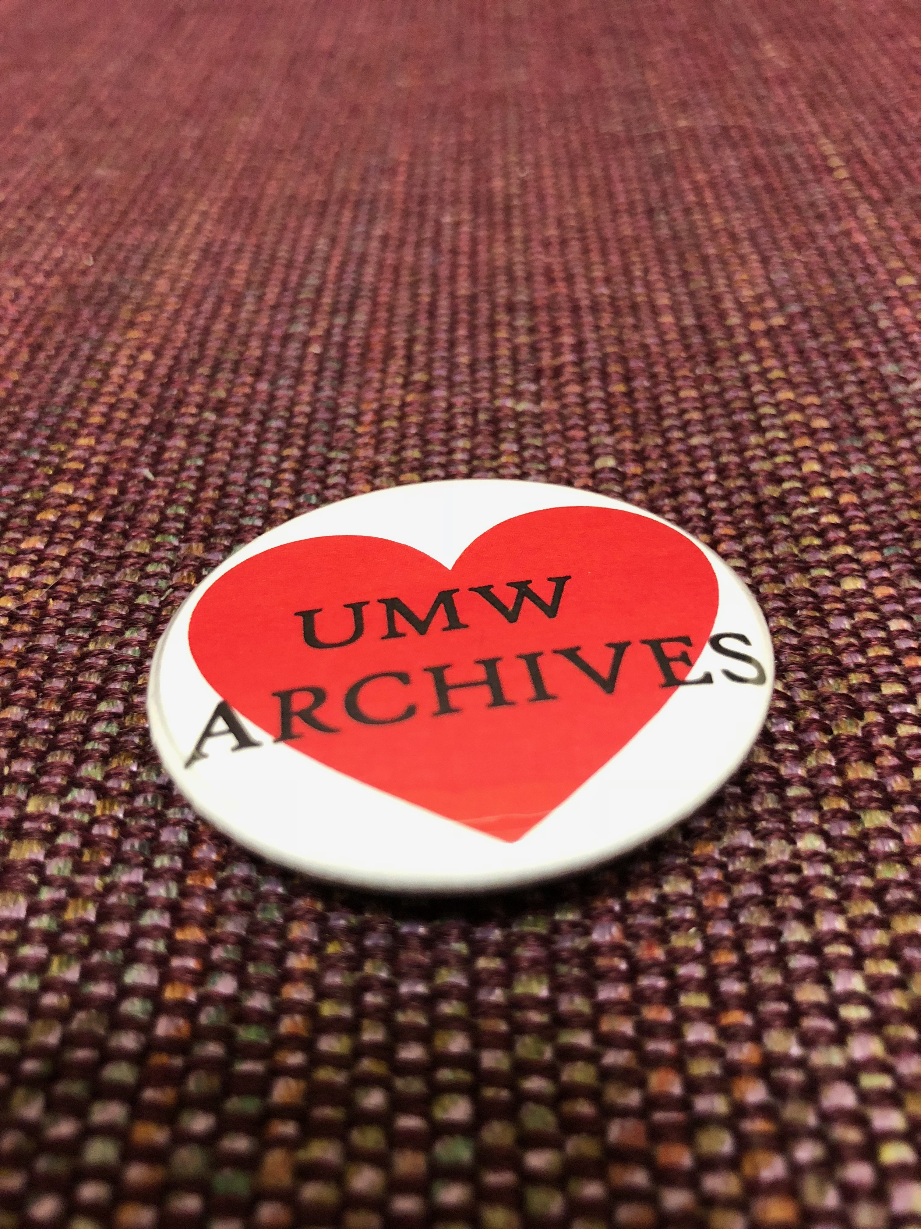 """Closeup image of a button that reads """"UMW Archives"""" inside a red heart."""