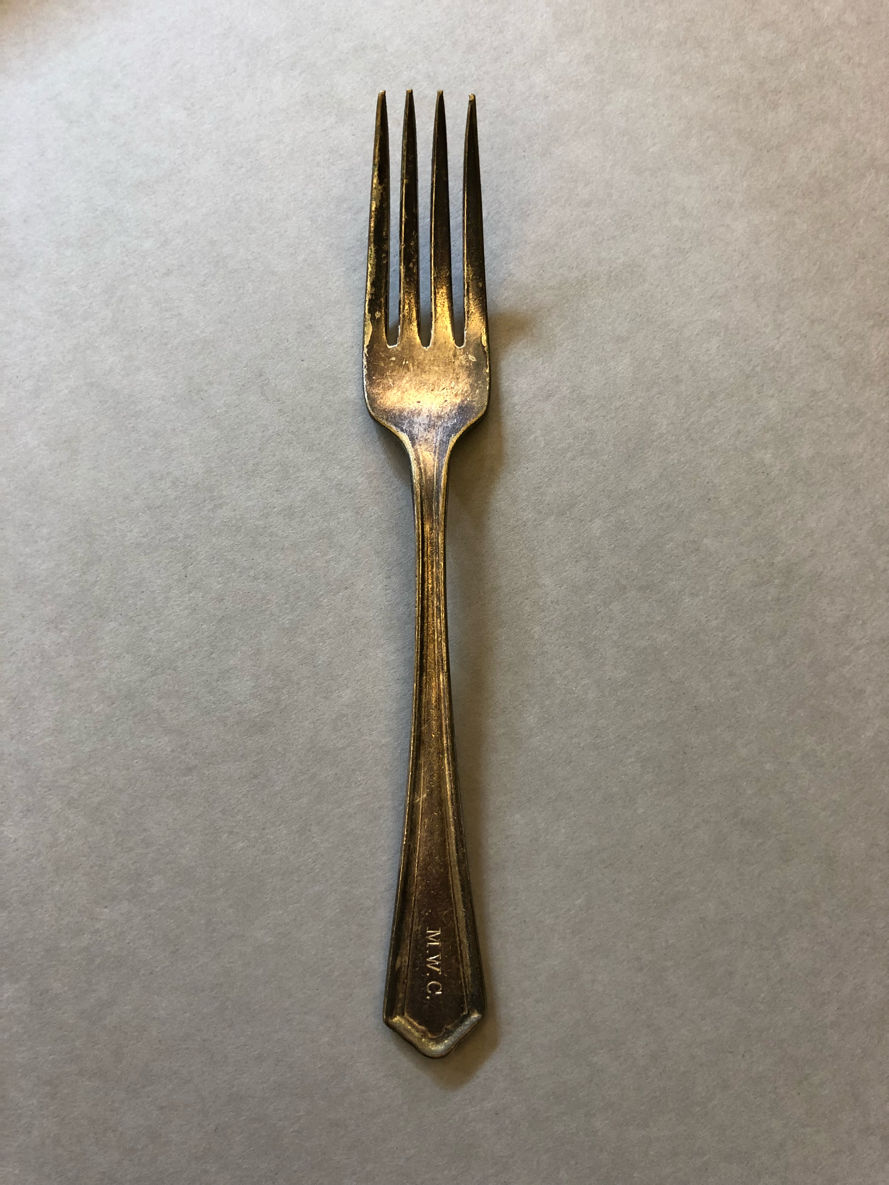 """A fork with """"MWC"""" stamped on the handle."""