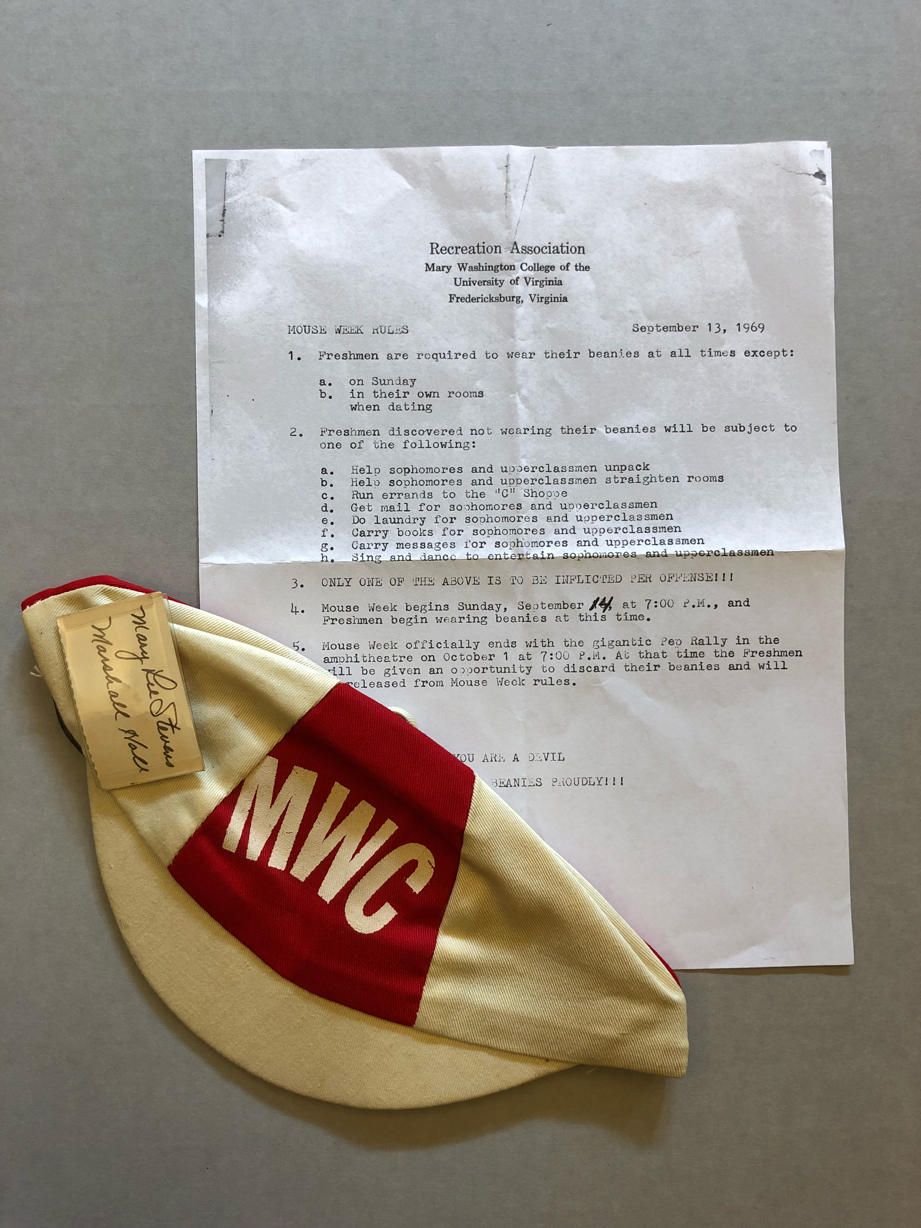 """Red and white MWC beanie with an attached handwritten nametag reading """"Mary Lee Stevens, Marshall Hall"""". The beanie partially covers a piece of paper titled """"Mouse Week Rules."""""""