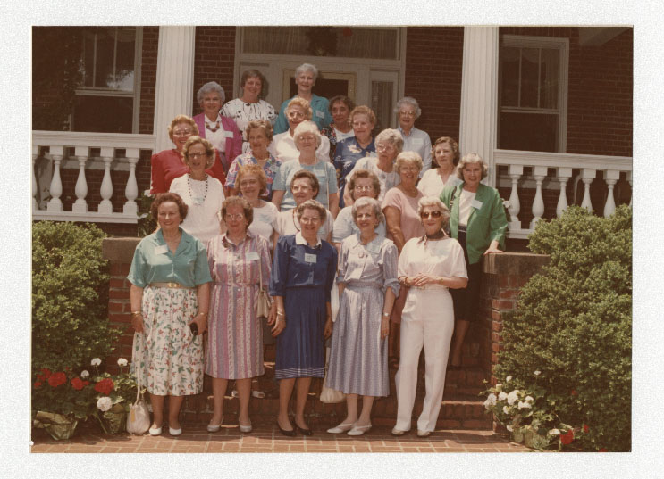 A photograph of about 23 alumni standing in front of a brick building for a group photo.