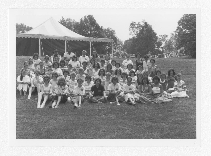 Photograph of a large group of alumni sitting and standing close together for a group photo. They are in front of a tent on a large, grassy hill.
