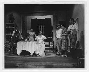 Four cast members sitting at a table with three casr members looking on from the right.