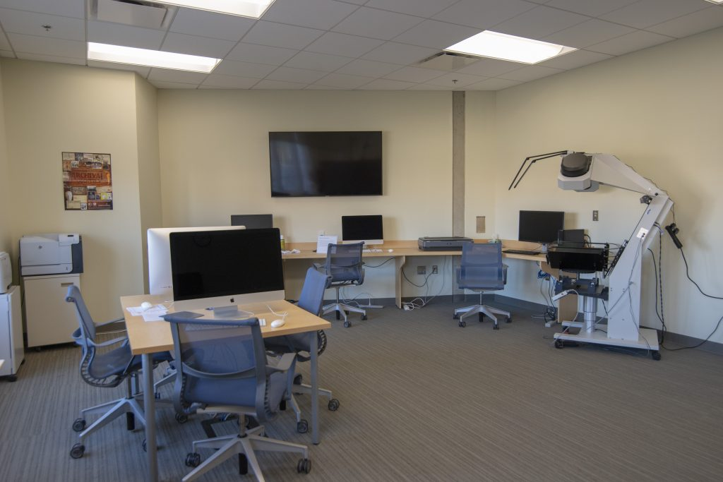Photograph of the Digital Archiving Lab, showing a room with computers, flatbed scanners, a large book scanner, and a large wall-mounted monitor.