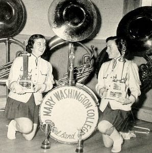 Two band members pose with the band's instruments and trophies.