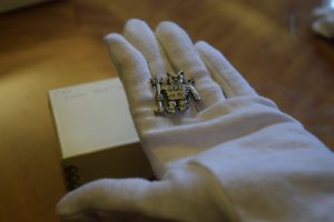 Photograph of a gloved hand holding a Devil-Goat Day devil pin.