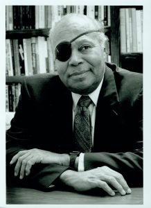 James Farmer seated at a desk in front of bookshelves.