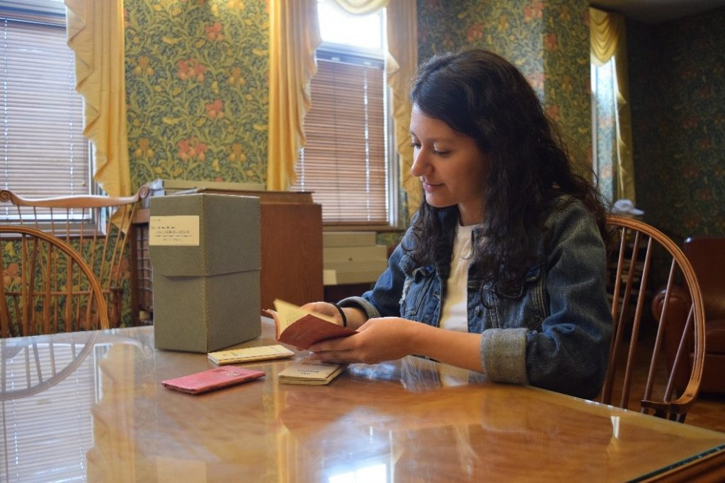 Photograph of student sitting at the reading room table, holding and studying small bound materials from University Archives.