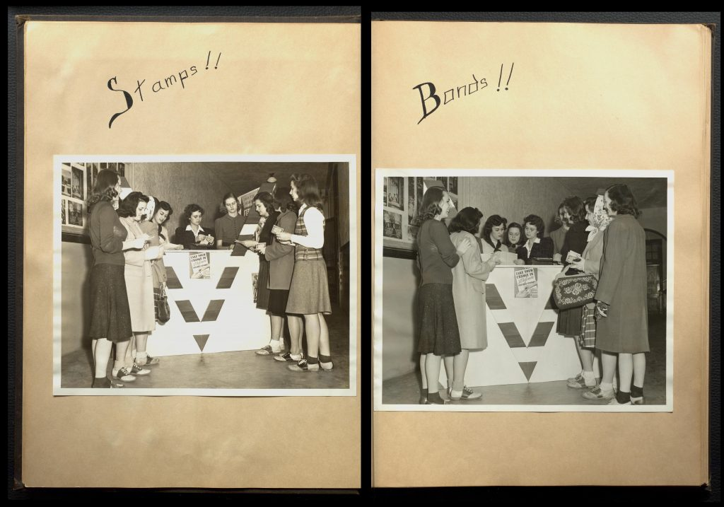 "One image showing both a left and right page of a scrapbook. One large black and white photograph is pasted on each page. In both photographs, a group of women are standing around a counter. The counter has a large ""V"" on the front of it. Above the photograph on the left page, the word ""Stamps!!"" is written. On the right page, the word ""Bonds!!"" is written above the photograph."