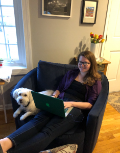 Student working on her online exhibit at home with white pet dog.