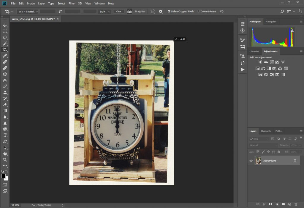 A screenshot of a photograph opened in Photoshop software. The screenshot depicts the straighten tool being used in Photoshop to straighten a crooked image. The image in Photoshop used for this example is of the clock installation in front of Woodard Hall.