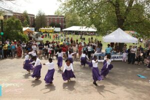 Women in purple and white costumesdance at an early Multicultural Fair.