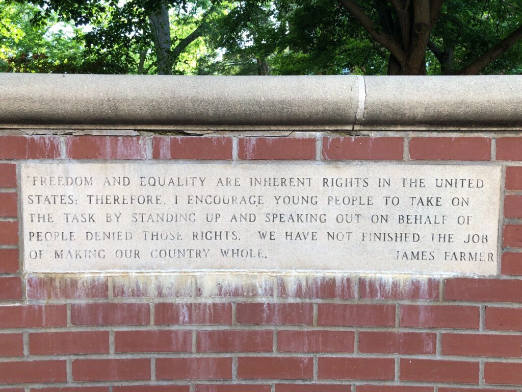 "Carving of a quote by James Farmer set in a brick wall. Quote reads, ""Freedom and equality are inherent rights in the United States. Therefore, I encourage young people to take on the task by standing up and speaking out on behalf of people denied those rights. We have not finished the job of making our country whole."""