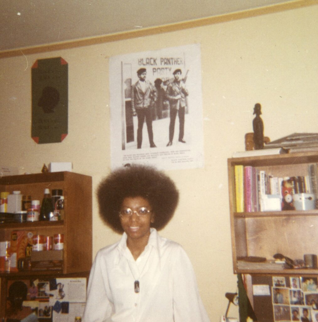 Black student in her dorm room with a Black Panthers poster hanging on the wall behind her.