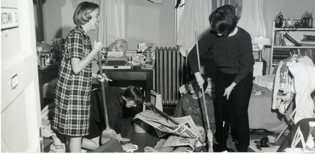 Four women clean their cluttered dorm room. Two are standing holding brooms, one is on hands and knees wiping the floor, and the fourth is seated reading a newspaper.