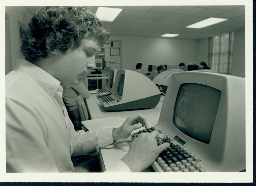 1980s-era man typing on a computer.