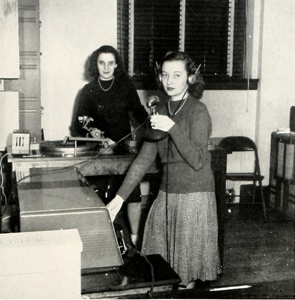 Students, Betty Sparks and Janet Ryder, stand at a microphone and turntable set-up in the WMWC Studio inside of George Washington Hall. One of the women is wearing headphones.