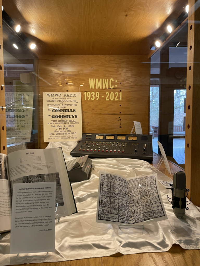 """Display case at Simpson Library with a label that says """"WMWC: 1939-2021."""" Included in the display are a yearbook, a zine, a large mixing board, a microphone, the Instant Replay cart replacement system, and a poster from a WMWC-sponsored concert of The Connells and The Goodguys from 1989."""