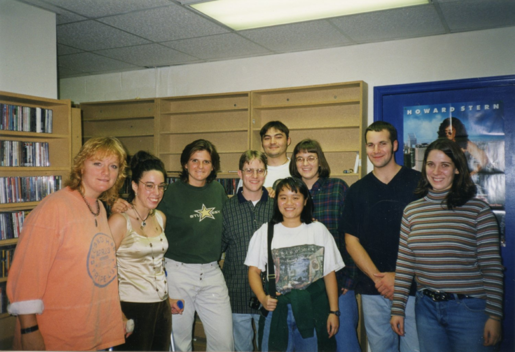 Musicians the Indigo Girls stand in the CD library of WMWC with six Mary Washington students and one visitor.
