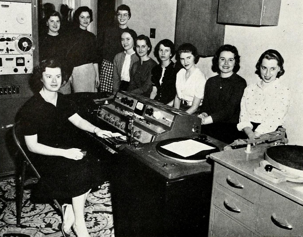Ten female students sit in the WMWC studio with a microphone mixing board, turntable, and reel-to-reel tape deck. One woman is sitting.