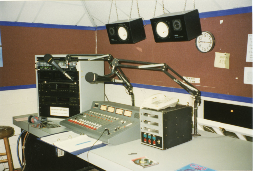 WMWC station in the attic of Lee Hall. Visible is a table with a mixing board, cart machine, tape deck, CD player, and speakers hanging from the ceiling.