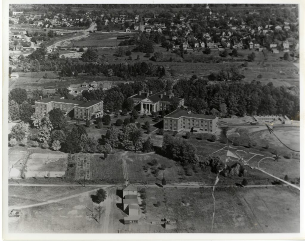 """An aerial view of campus as it appeared in 1928. Willard, Monroe, and Virginia Halls are visible, as are the construction sites for Lee and Chandler Halls. The letters """"FSTC"""" appear in large letters on the lawn below Virginia Hall."""