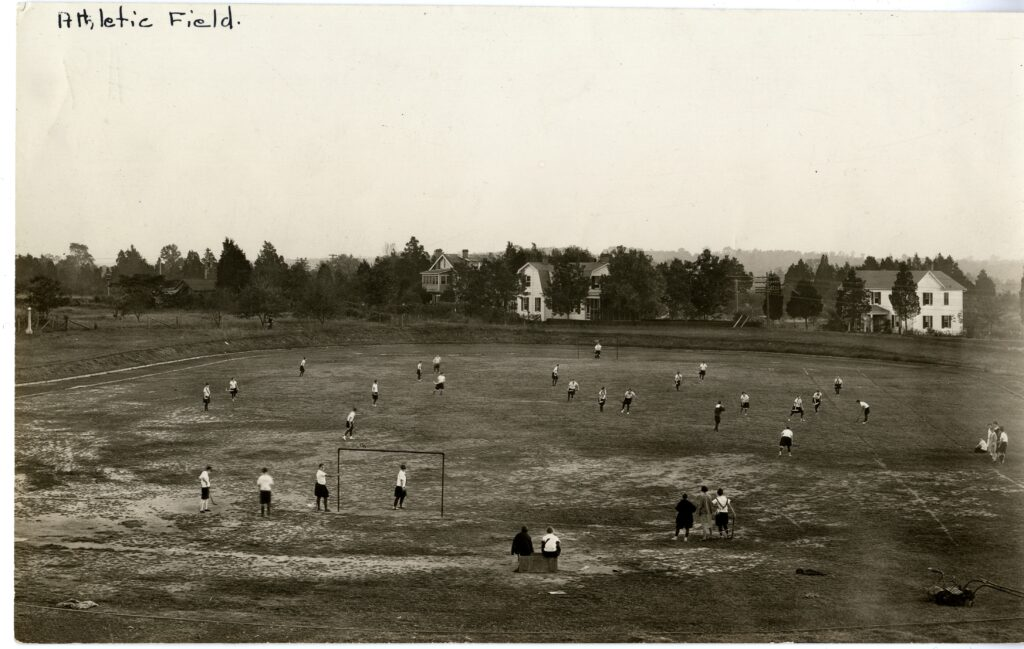 About thirty students engage in unspecified physical activities on an athletic field, circa 1925.