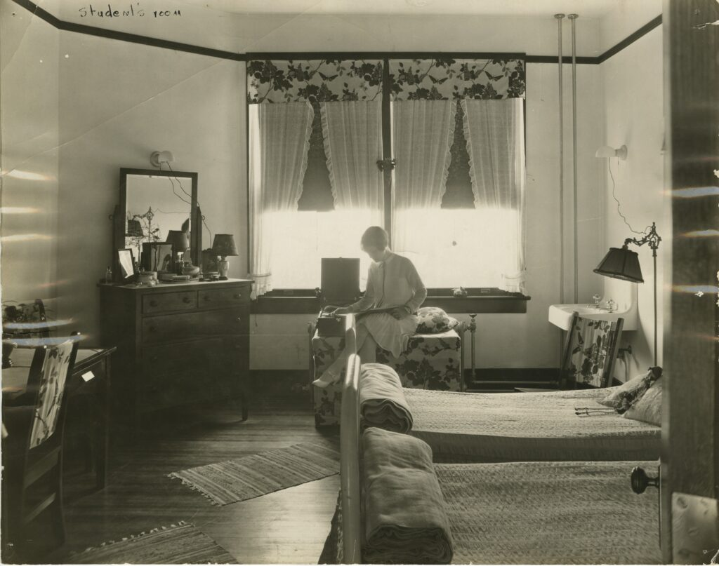 A woman sits alone in a double-occupancy dorm room, backlit by the windows behind her.