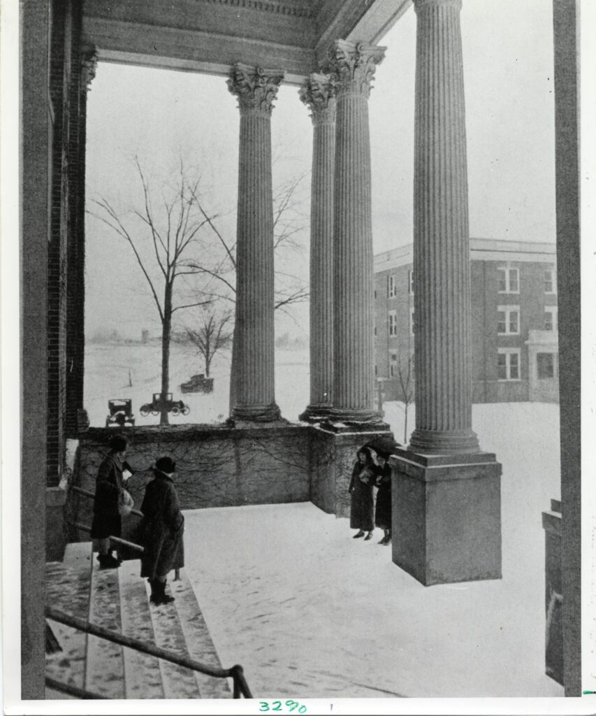 A 1920s exterior view of the Monroe Hall portico covered in snow as four women gather on the steps.