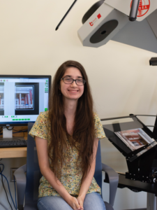 A photograph of Francesca sitting in front of the Cobra scanner and its attached computer.