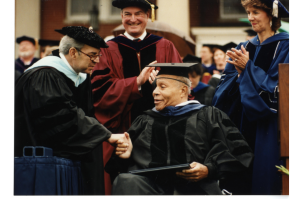 James Farmer smiles and shakes President Anderson's hand upon receiving his honorary degree at the 1997 Commencement.