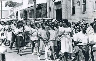 A large group of predominantly Black people depicted marching through a city street.
