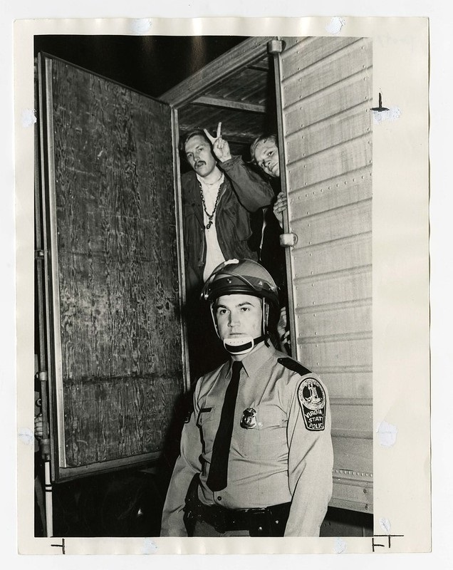 Two people standing in a door frame, one holding up the peace sign gesture with his fingers. In the foreground is a uniformed police officer.