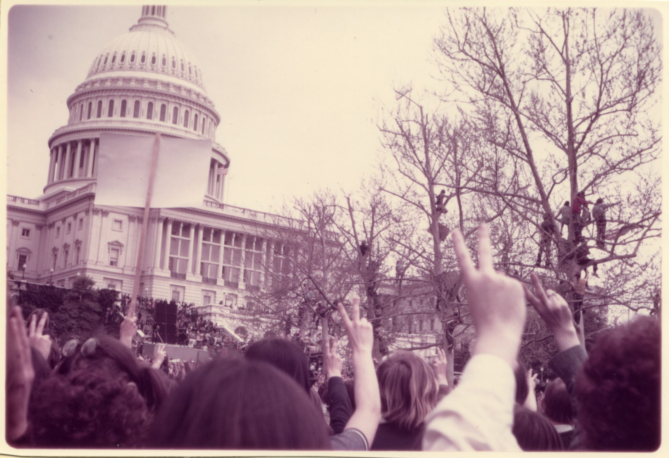 A large group of people standing outside the US Capitol building holding up their fingers in peace sign gestures.